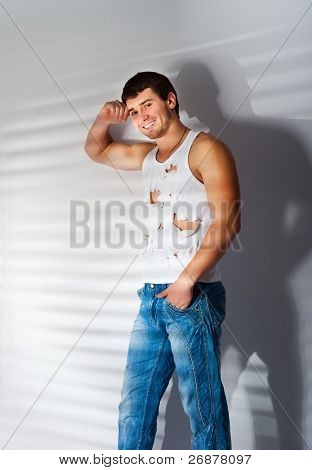 muscular  man in torn white top and jeans hands in pockets looking up