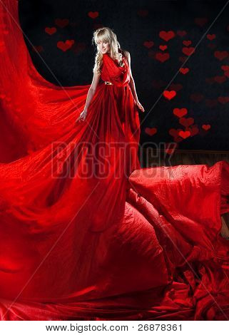 Perfect blonde in a red dress on black background