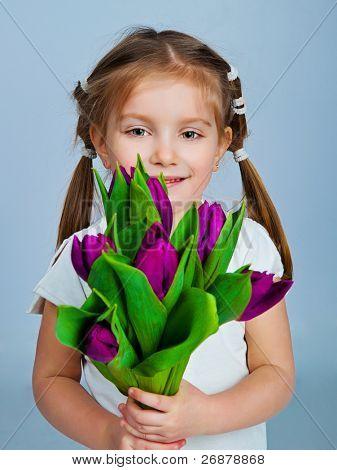 Cute little girl giving tulips. Studio shot