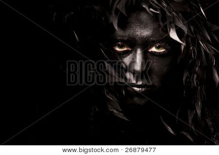 Close up portrait of evil spirit with green eyes, isolated on black