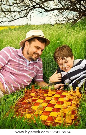 Father and son playing chess outdoors