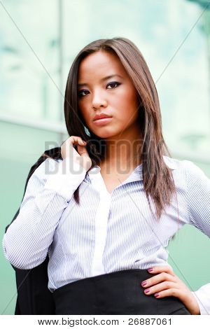 Thoughtful young beautiful asian businesswoman in front of business building