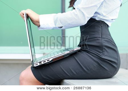 woman on the street sitting with a laptop computer in her lap and typing