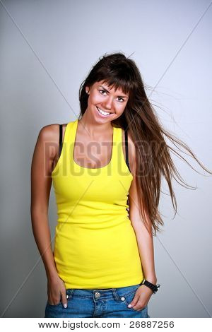 Laughing sexy woman in yellow t-shirt with wind