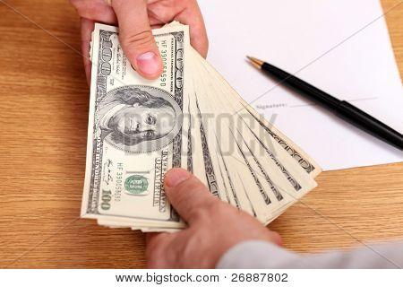 Geschäftsleute Geld mit Vertrag im Hintergrund übergeben