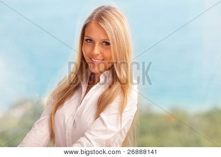 Strikingly beautiful woman with a happy smile sitting at home. Seaview in the background