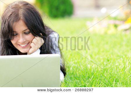Young beautiful smiling woman using laptop on campus/home yard. Sunny day.