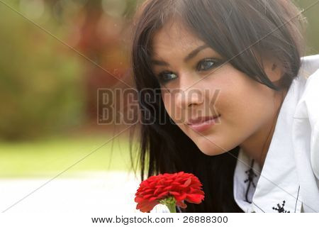 Happy young dreamy beautiful woman lying on the grass with red flower. Sunny day.