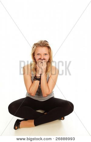 Young surprised girl sitting on the floor, isolated on white background