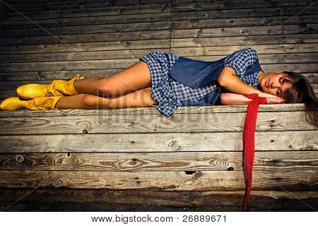Young beautiful lady in fashion cloths sleeping on the bench in the park