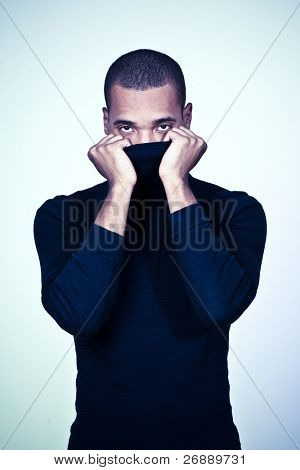 Young hiding african-american man in black sweater isolated on white background