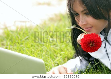 Happy young beautiful woman lying on the grass with laptop and red flower. Sunny day.