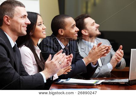 Multi ethnic business group greets somebody with clapping and smiling. Focus on woman