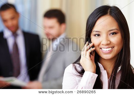 Portrait of young happy asian woman on phone with her business partners on the background