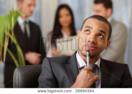 Pensive african-american businessman with his team working behind