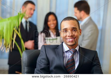 Happy african-american businessman with his team working behind