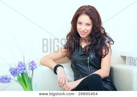 Beautiful rock-n-roll woman sitting on a sofa