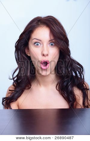 Portrait of a surprised young female fashion model posing