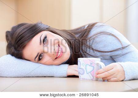Jovem feliz na camisola quente bebendo uma xícara de chá quente