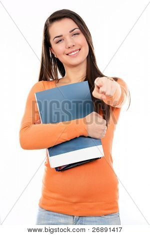 Young student with her books in hand pointing on you, smiling and looking at the camera