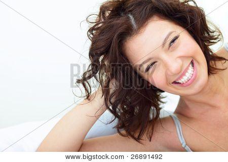 Hermosa mujer tumbados en el sofá y riendo sinceramente
