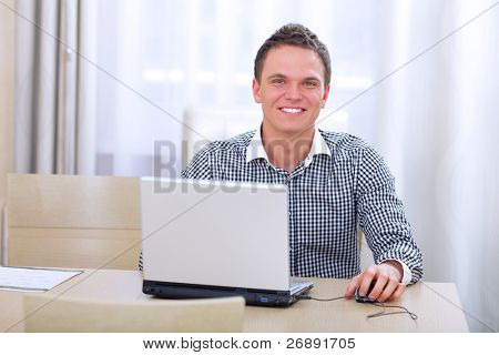 Closeup of happy young businessman using laptop
