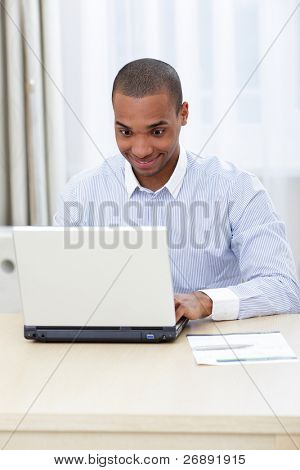 Young business man with a shocked expression working on a laptop