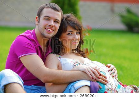 Happy beautiful pregnant woman with his husband sitting on the lawn outside