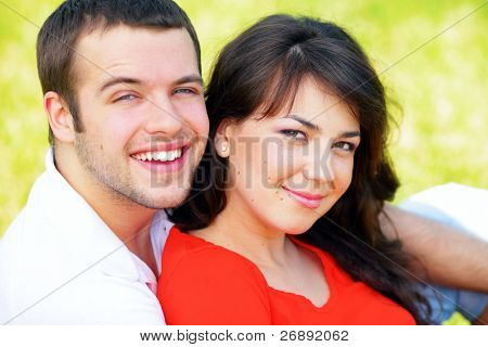 A portrait of a sweet couple in love embracing outdoors. Focus on woman.