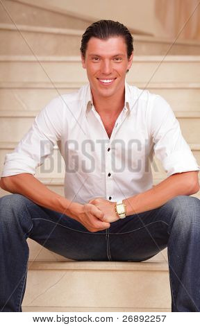 Portrait of handsome young man sitting on the stairs at home