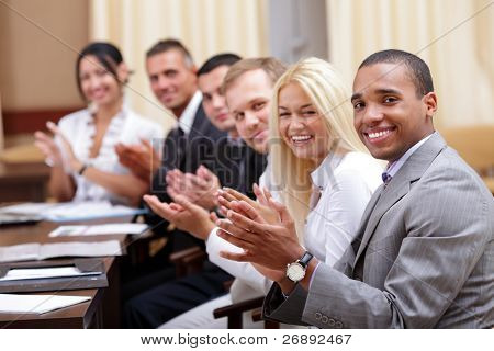 Multi ethnic business group greets you with clapping and smiling