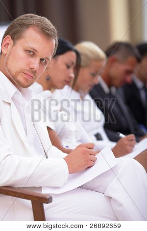 Business people sitting in a row at meeting and making notes
