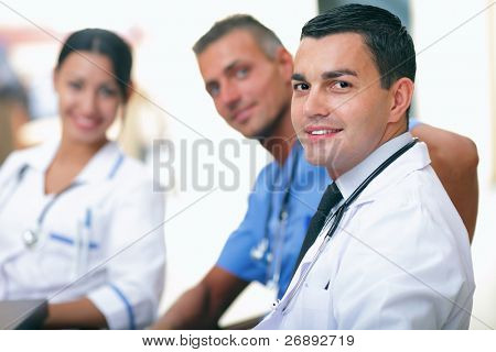 Portrait of a smart young male doctor sitting in front of his team and smiling