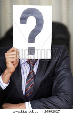 The new worker holds the white paper with question sign in front of his face