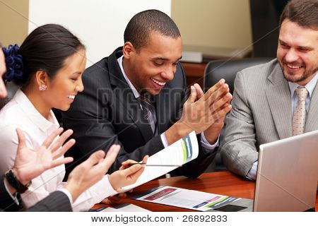 Multi ethnic business team at a meeting. Interacting. Focus on african-american man