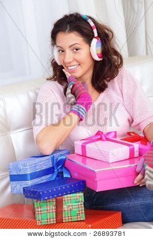 Feliz mujer joven excitada en casa con muchos presenta