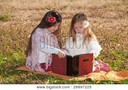 Two little girls read the book while sitting on the grass.