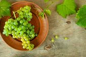 Ripe Grape Cluster Of White Grapes In A Bowl On A Wooden Table With Green Leaves Of Grapes. Vintage  poster