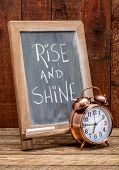 Rise and shine  sign - white chalk handwriting on a blackboard  with an alarm clock against rustic b poster