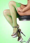stock photo of fetish fishnet stockings  - Female legs in green fishnet stockings against green background - JPG