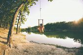 Jump Into The Water. A Man Is Resting On The Lake. A Swing From A Rope And A Stick. Active Recreatio poster