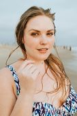 Confident blond plus size woman at the beach poster