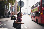 Woman with braids crossing a street in downtown London poster