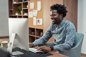 Portrait of african american businessman using computer at desk. Handsome employee enjoying work in  poster