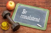 Be consistent concept -  slate blackboard sign against weathered red painted barn wood with a dumbbe poster