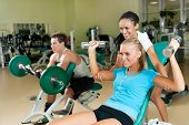 image of personal trainer  - Young woman lifting a dumb - JPG
