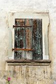 Rustic Faded Vintage Wooden Window Shutter Set In A Stone Wall poster