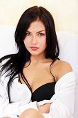 stock photo of breast exposed  - Young beautiful woman sitting on the sofa with bra exposed - JPG