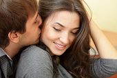 image of kissing couple  - Young man kisses his beautiful girlfriend - JPG
