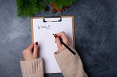 Woman Hands Ready To Write Goals On Blank List On Dark Background. Flat Lay. Top View. New Year Conc poster